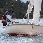 adults sailing a boat