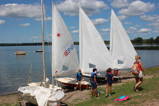 kids getting ready to sail on the beach