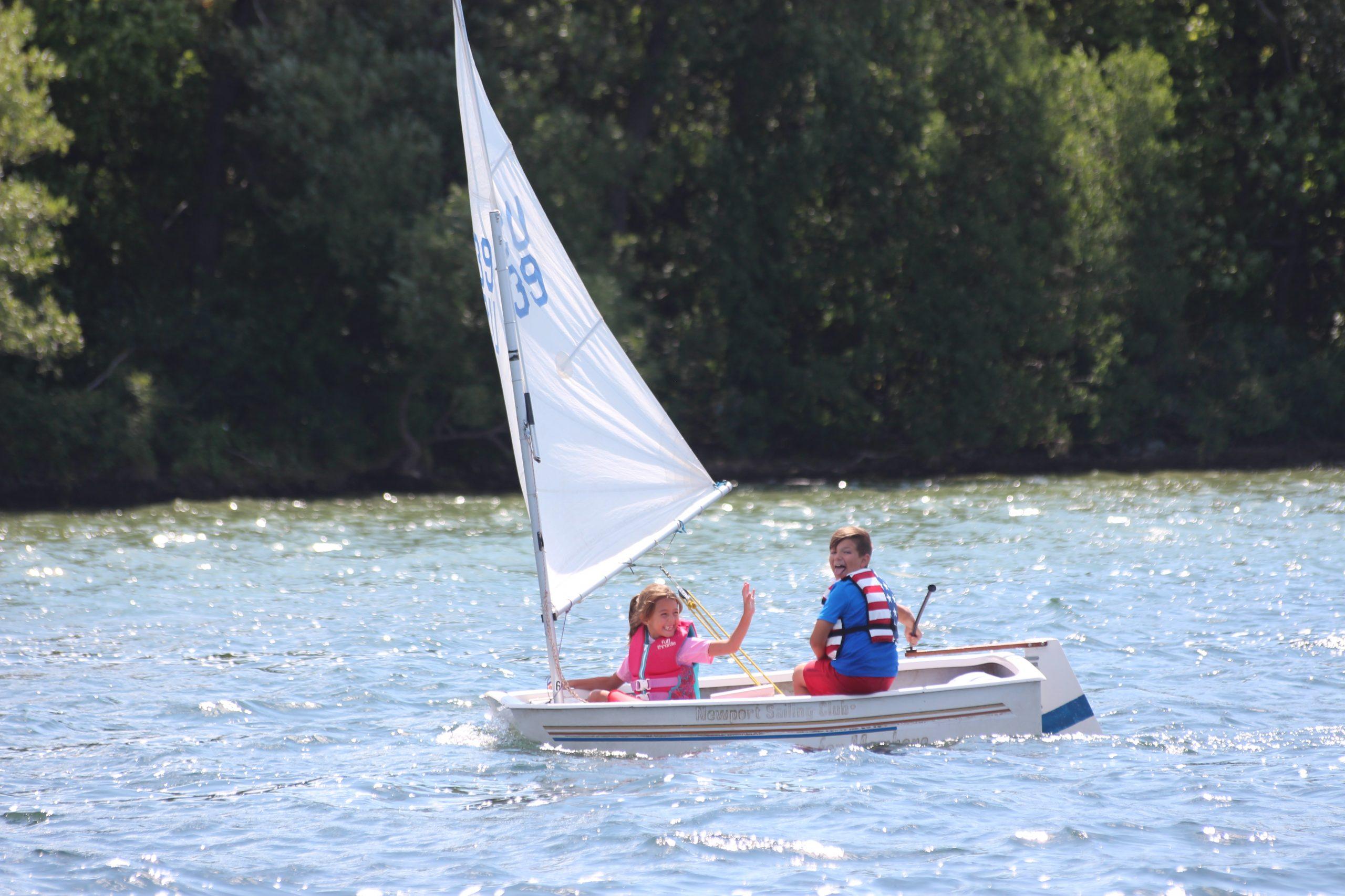 Kids sailing in an Optimist Pram sailing dinghy