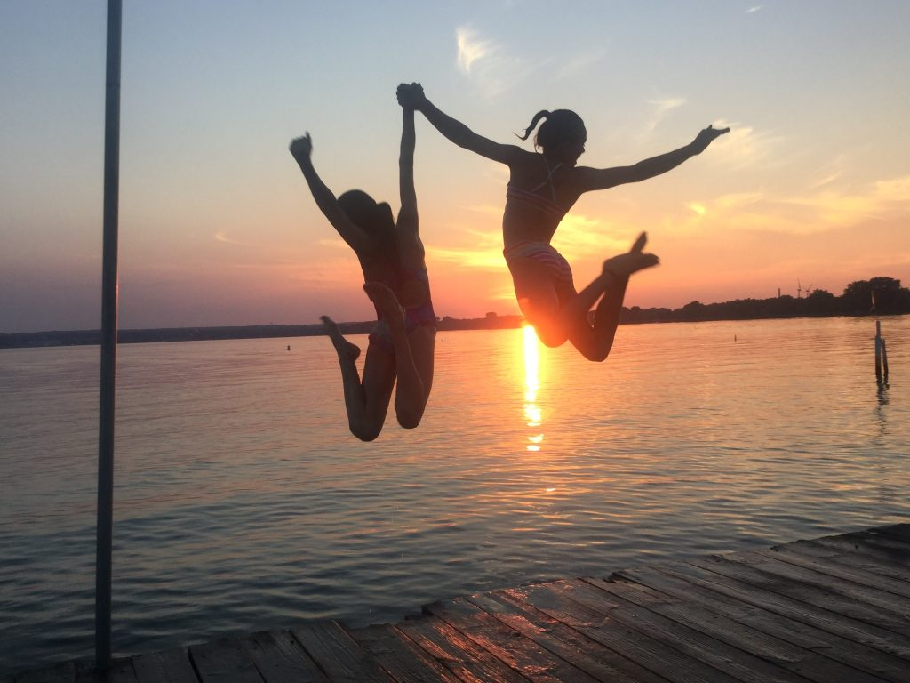 Silhouetted kids jumping at sunset